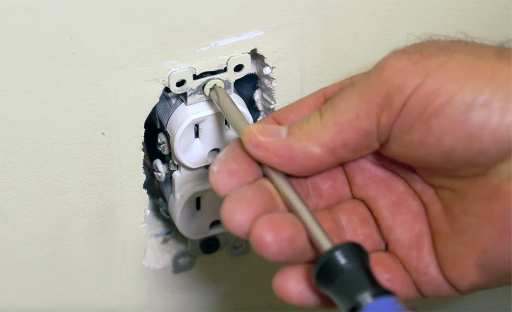 A person unscrewing an electrical outlet.