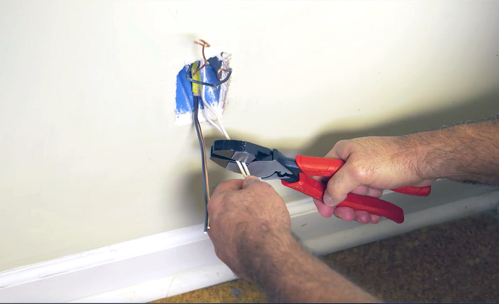 A person trimming wires from the wall box with a wire cutter.