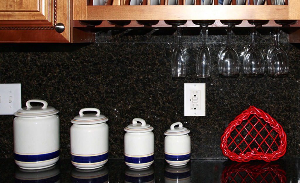 A GFCI outlet installed on a kitchen counter wall.