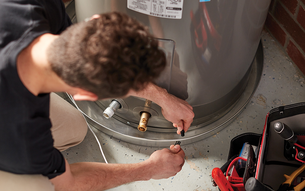 A man removing a water heater.