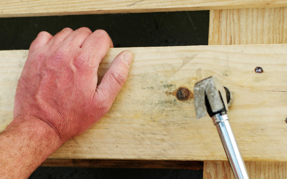 A person using a hammer and lumber to mount a gas tankless water heater.