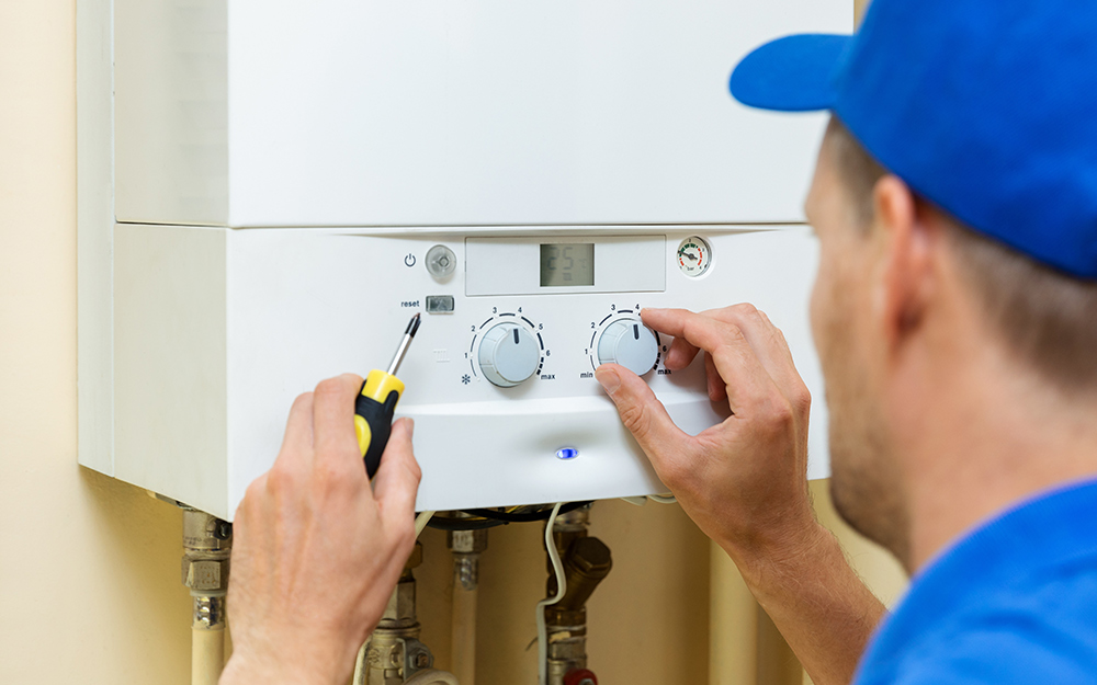 A man turning on and adjusting the settings for a gas tankless water heater.
