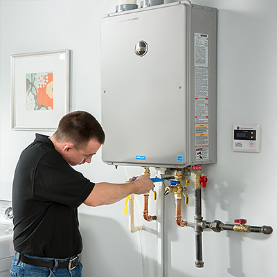 A man installing a gas tankless water heater.