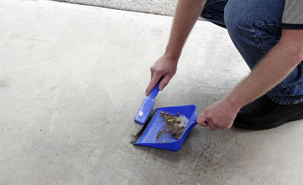 Man sweeping up subfloor before installing tile.