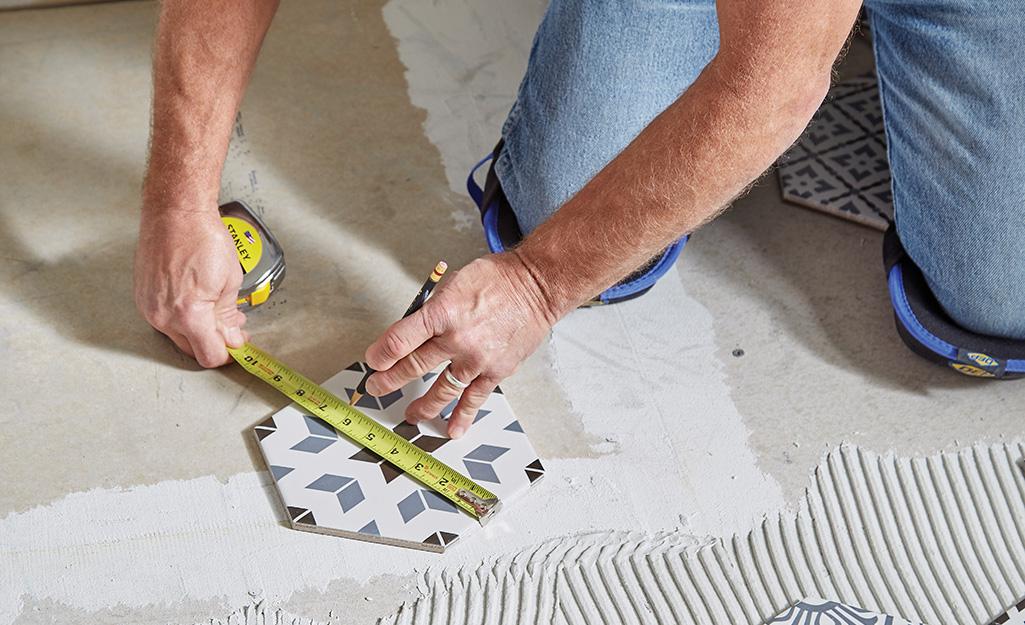 Man measuring tile.