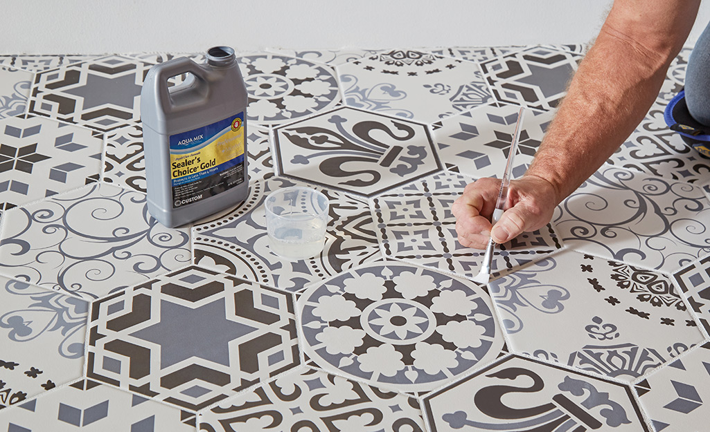 Person sealing grout using a small brush.