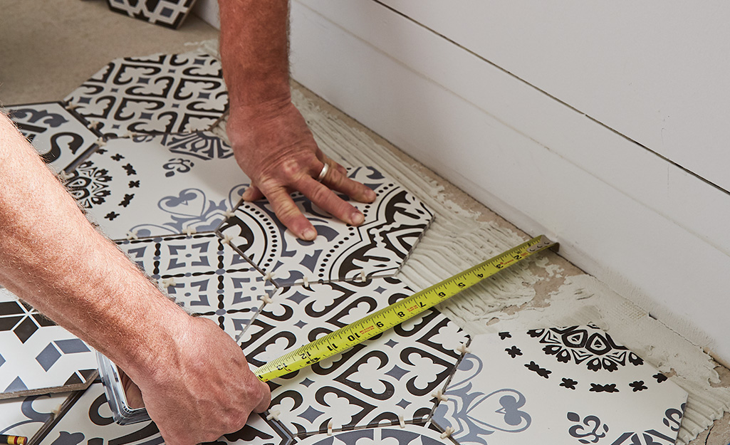 Someone measuring tile and floor.