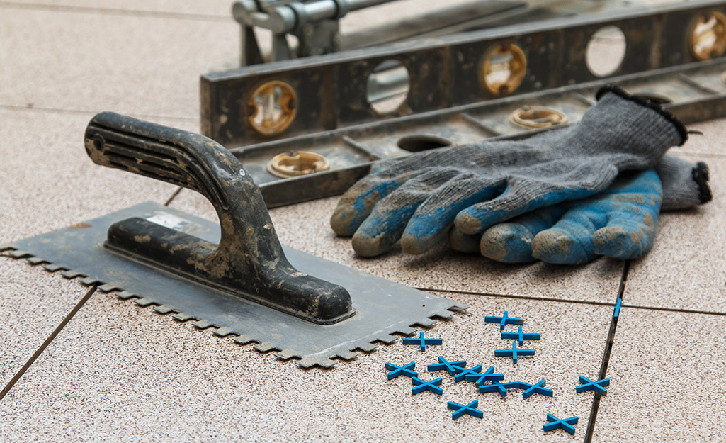 A trowel, spacers and level placed next to work gloves.