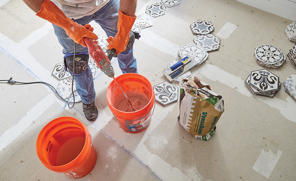 Person mixing grout in an orange Homer bucket.