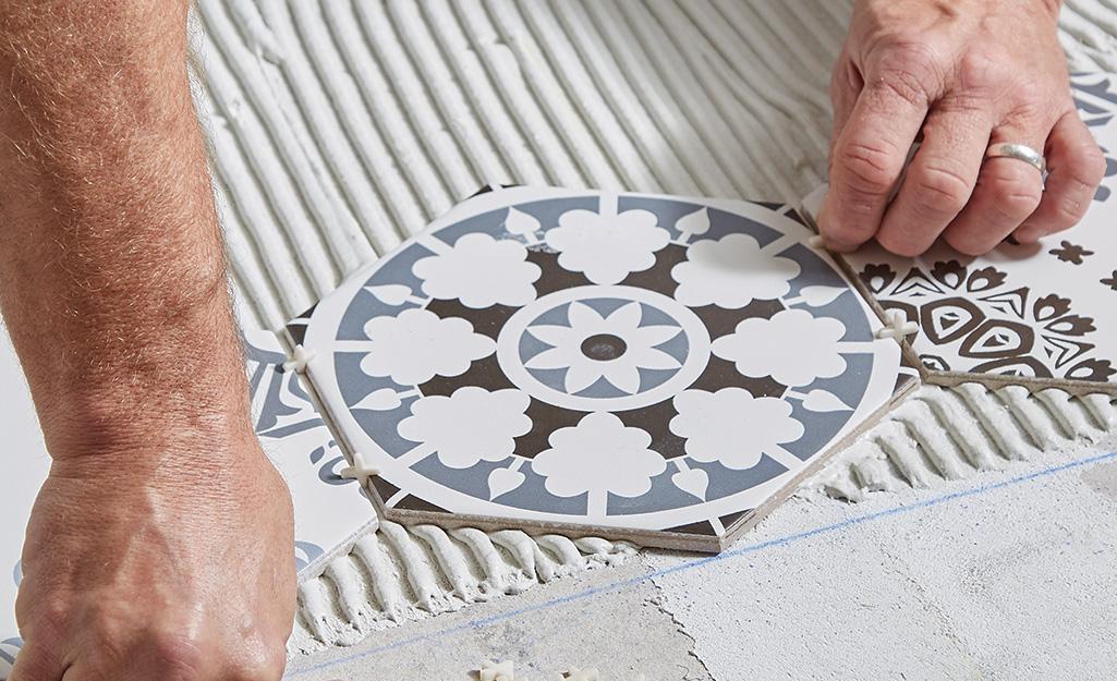 Man adding spacers between round tiles.