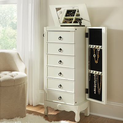 A white jewelry armoire in a bedroom.