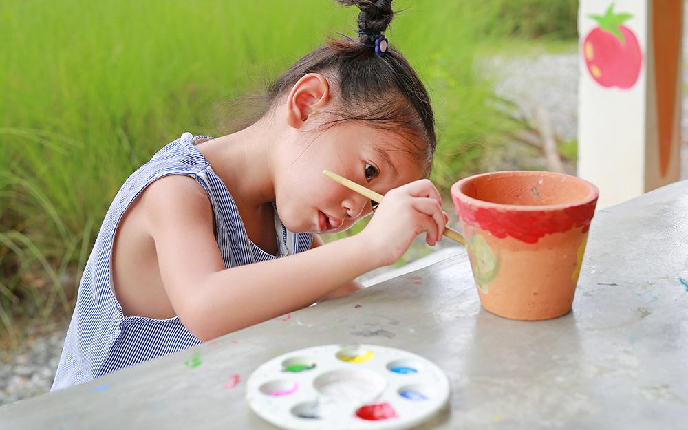 Cậu bé vẽ chậu hoa bằng đất sét