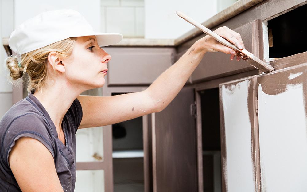 Một người phụ nữ sơn tủ bếp