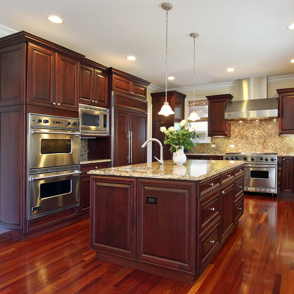 A large kitchen featuring beautiful wood cabinets in a dark finish.