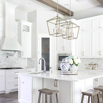 A kitchen with white cabinets and a large island with wooden stools.