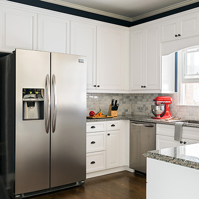 A kitchen with white cabinets and stainless steel appliances.