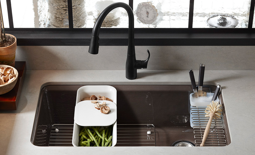 A brushed metal kitchen sink with a black faucet.