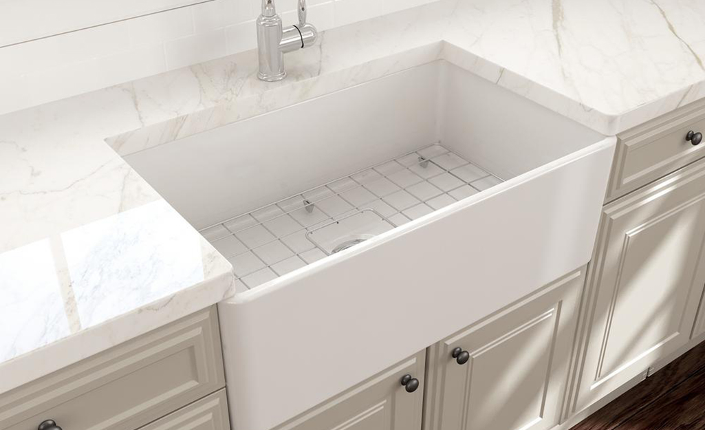 A deep apron sink with a wire dish grid set inside.