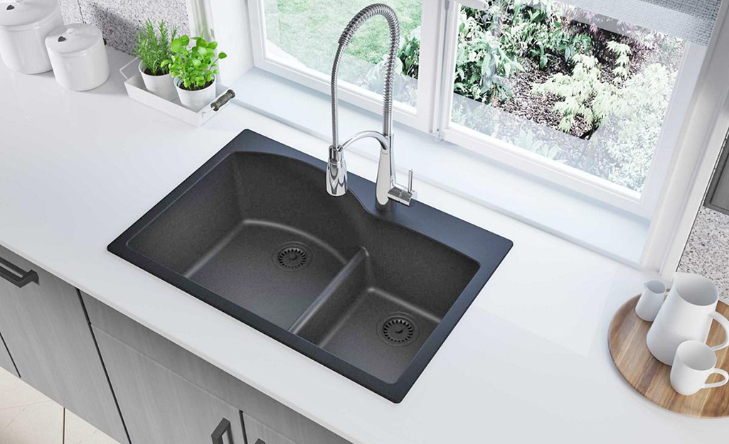 A black double-bowl kitchen sink in a white countertop.