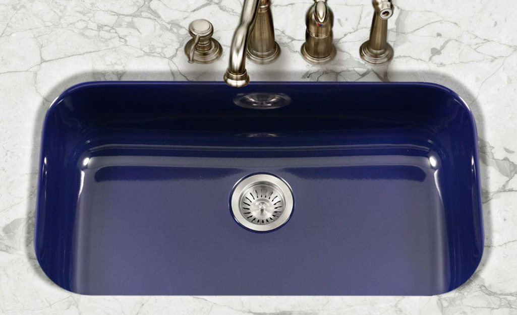 A blue single bowl sink with four tappings for a faucet, sprayer and soap dispenser.
