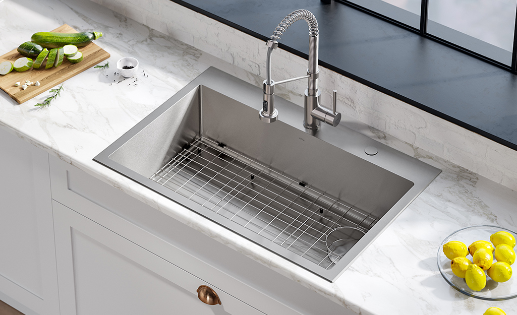 An all-in-one stainless steel kitchen sink with a pull-down faucet on a white countertop.
