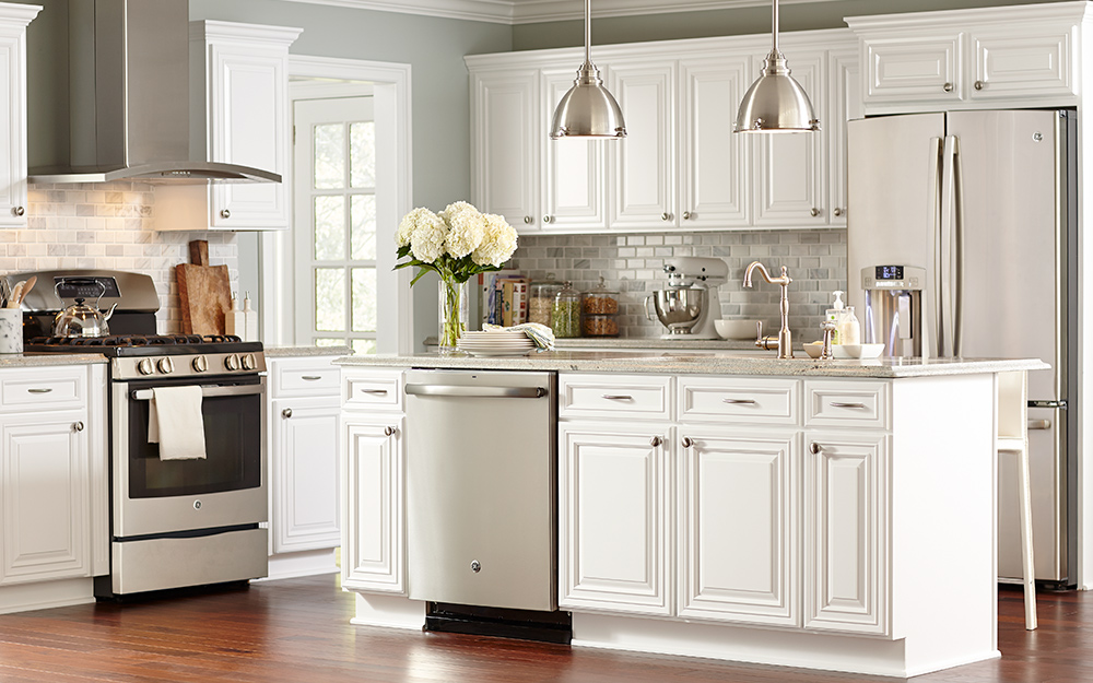 A Kitchen With White Cabinets And Silver Hardware