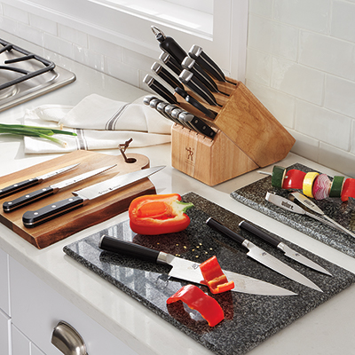 A variety of kitchen knives and wooden storage block on a countertop.