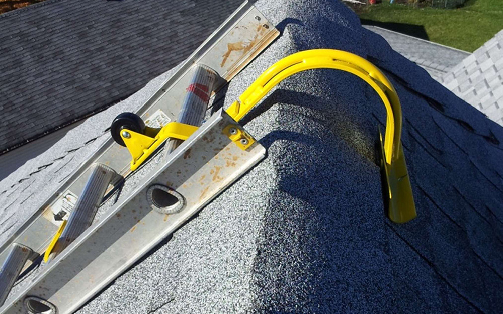 A ladder atop a roof with a ladder hook attached