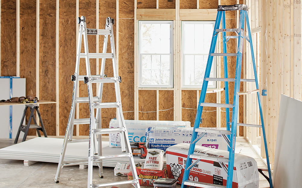 Two different ladders in an unfinished room