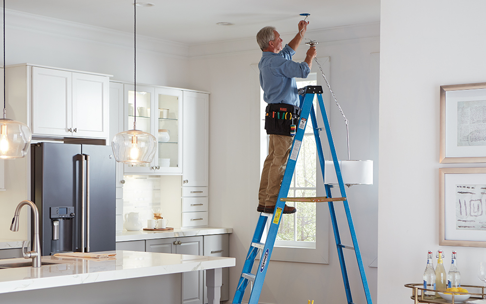 A man standing on a ladder working on a ceiling fixture