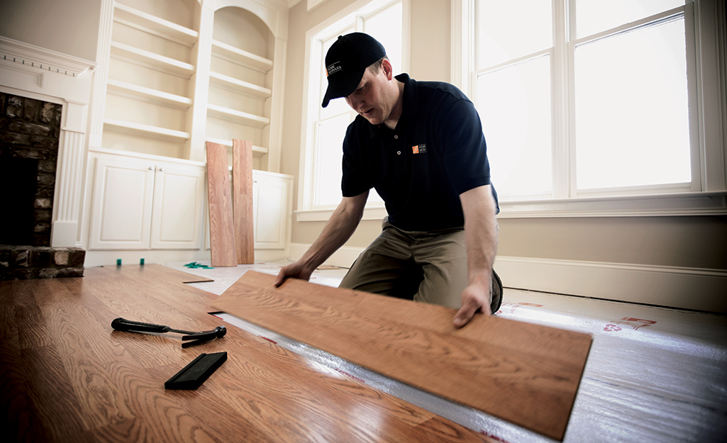 Man installing laminate flooring.