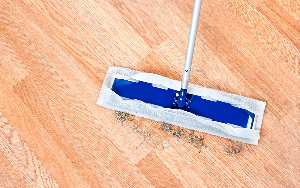 A cleaning tool removing dirt from a light wood-colored laminate floor.