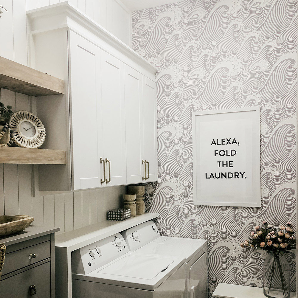 A laundry room with white upper cabinets and open shelving.