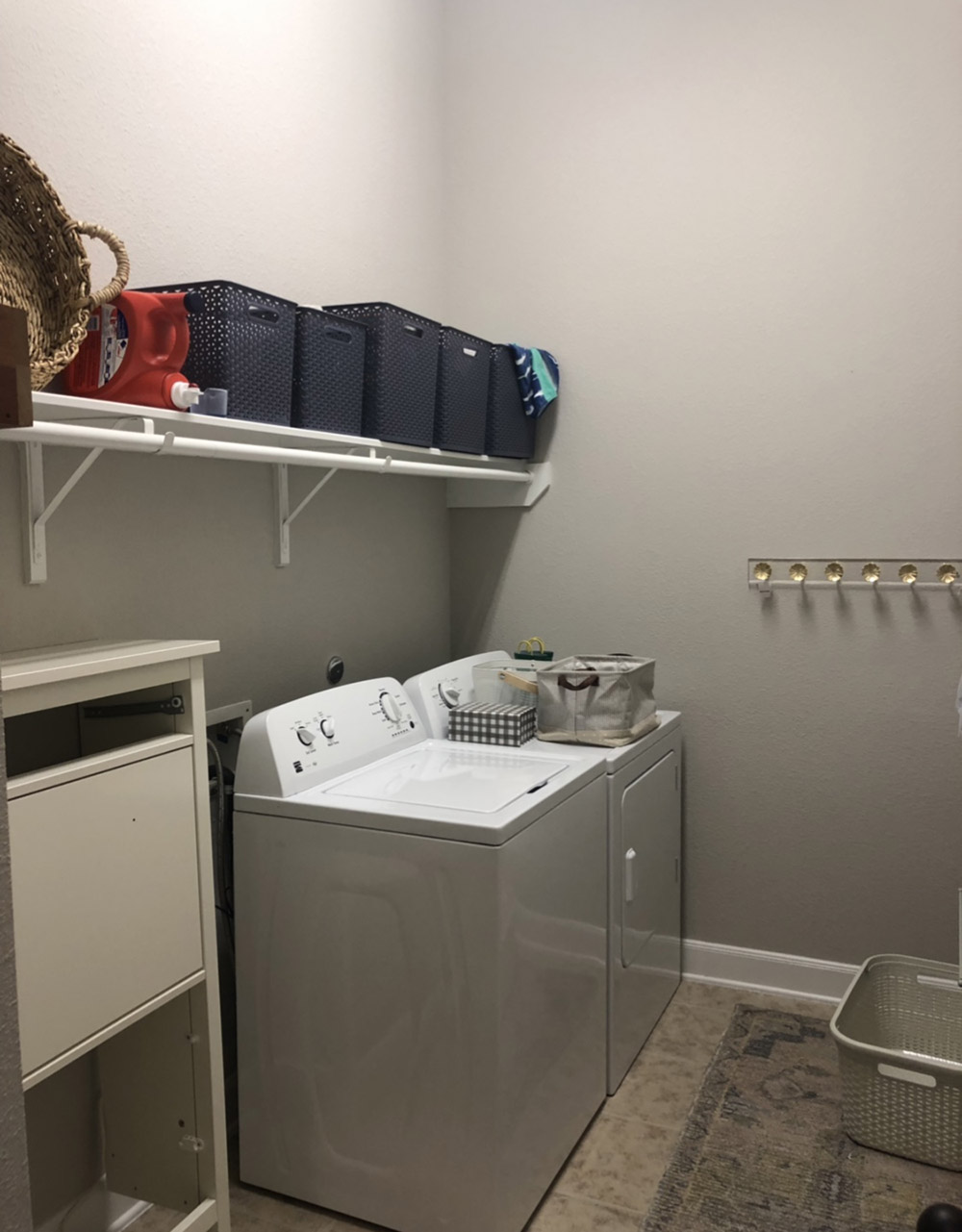 A plain laundry room with only one wall shelf.