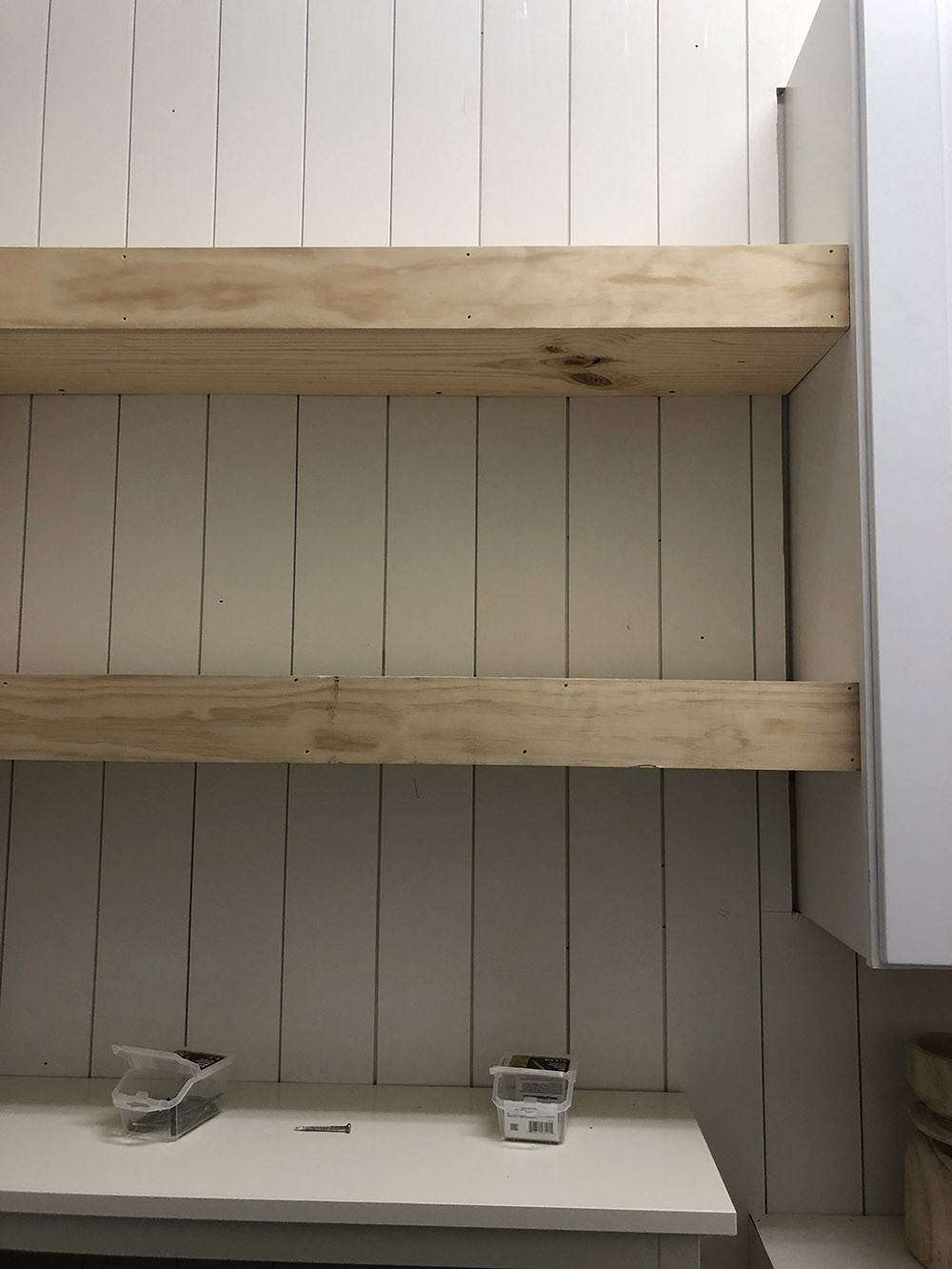 A wall with white vertical shiplap and two floating shelves.
