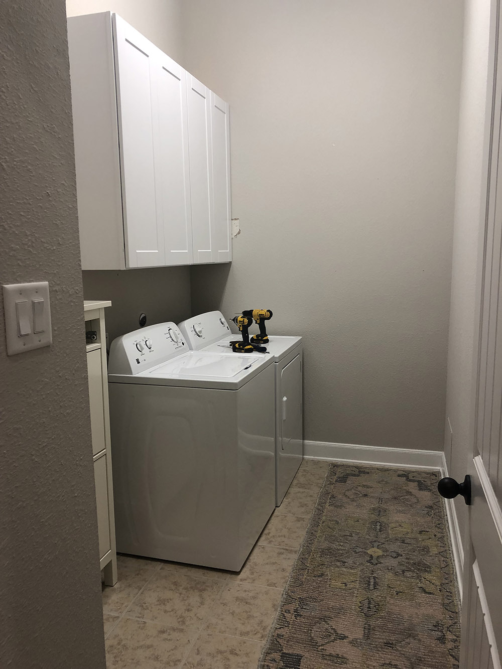 A pair of white cabinets mounted on a wall above a washer and dryer.