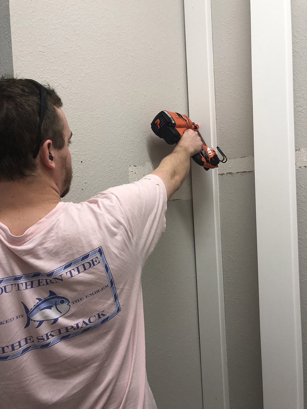 A man installing white vertical shiplap on a wall.