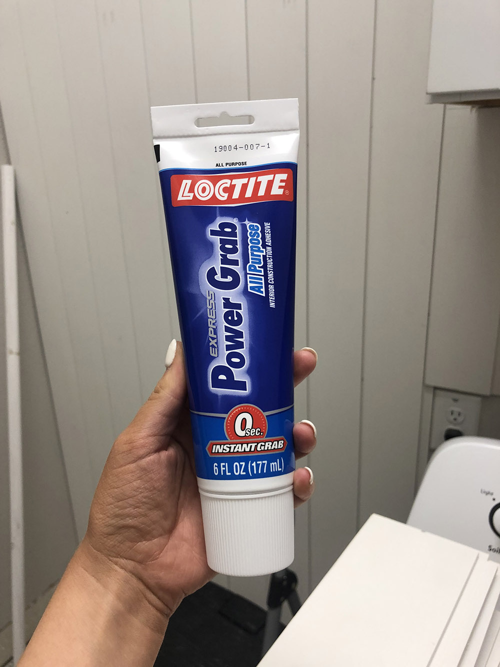 A person holding a tube of Loctite power grab.