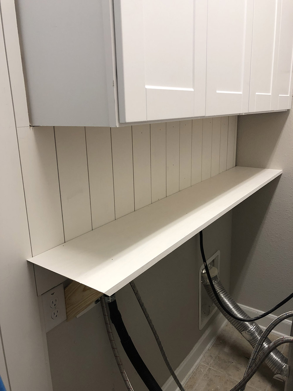 A laundry room wall with a shelf supported by four angled wood supports.