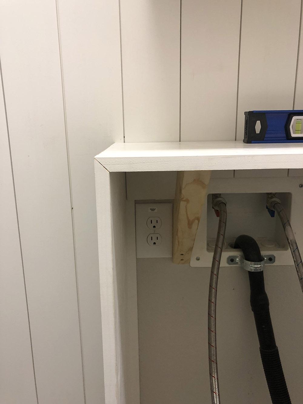 A white shelf covers laundry cords.