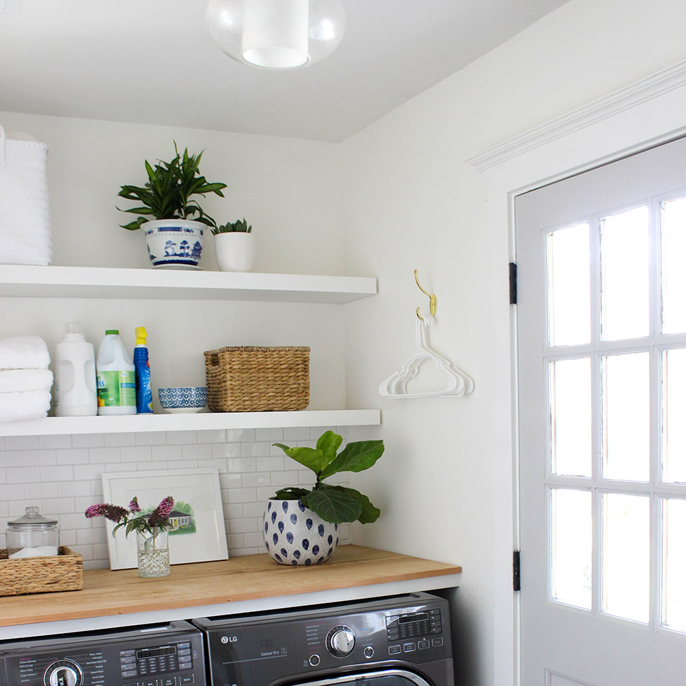 A laundry room with white walls, white floating shelves, and a butcher block counter.