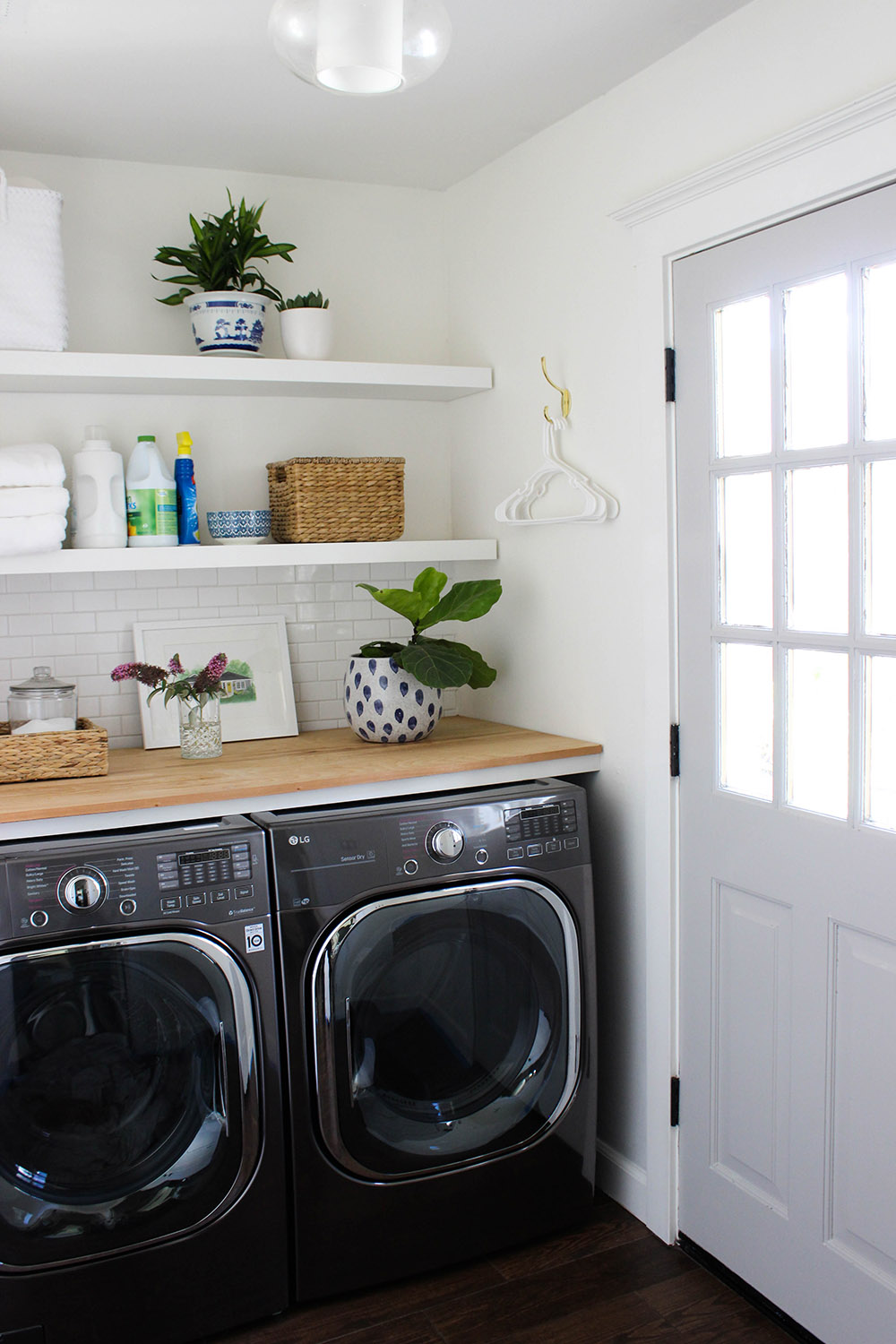 A laundry room with black front load laundry appliances.