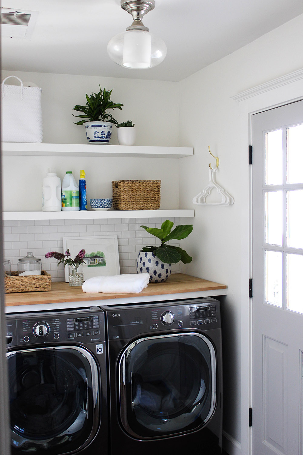 A completed laundry room refresh with new LG front load laundry appliances.
