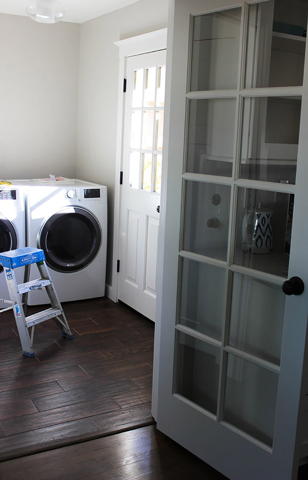 A laundry room with white front load laundry appliances and no storage.