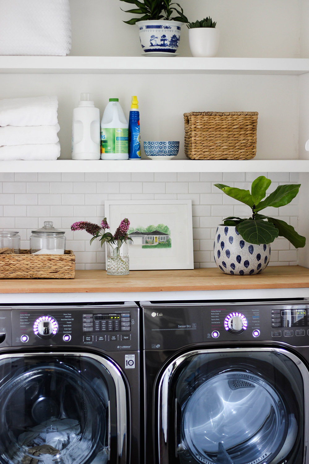 An updated laundry room with shelving, tile backsplash, and a butcher block counter.