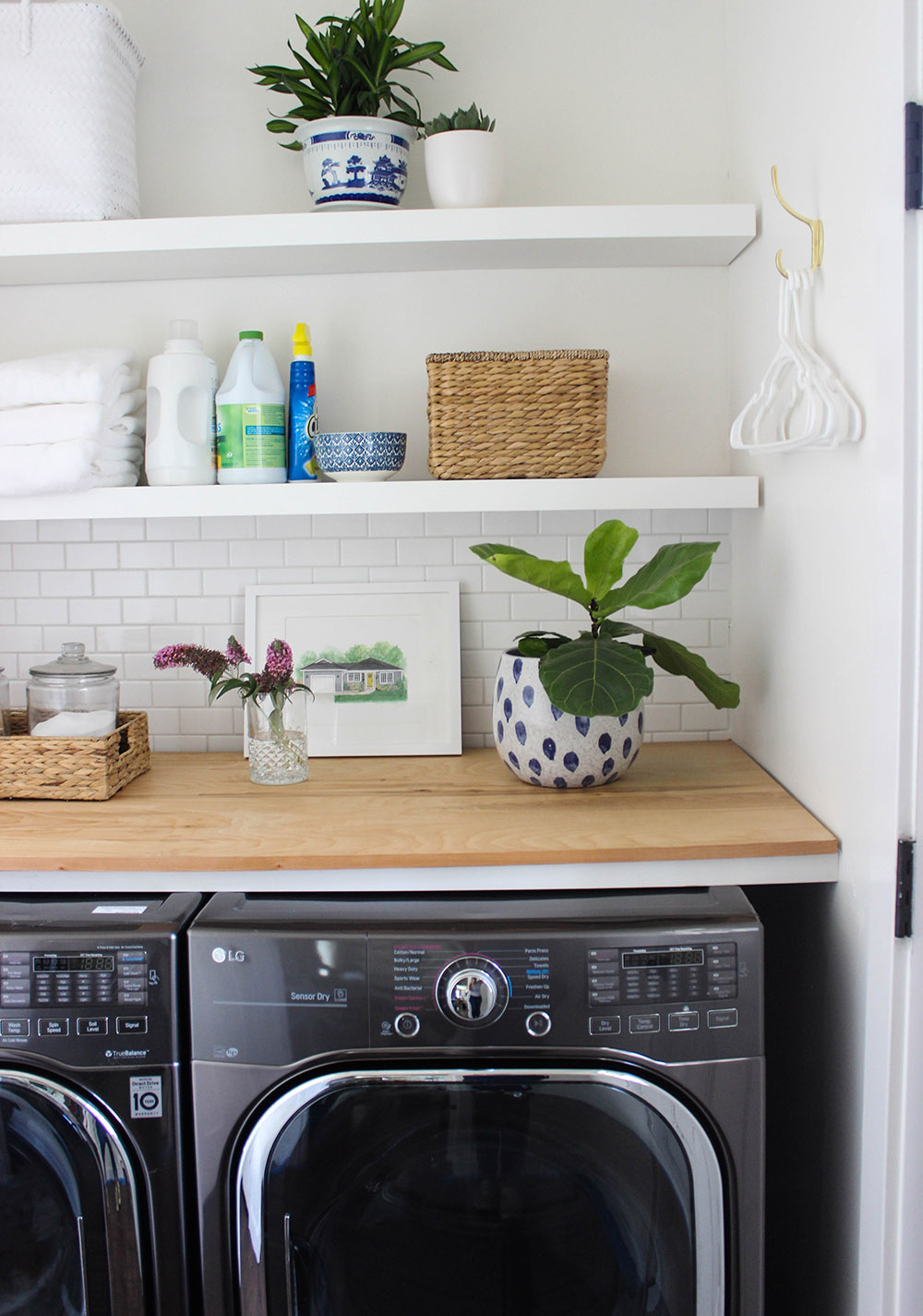 A butcher block counter sits above a black LG washer and dryer.