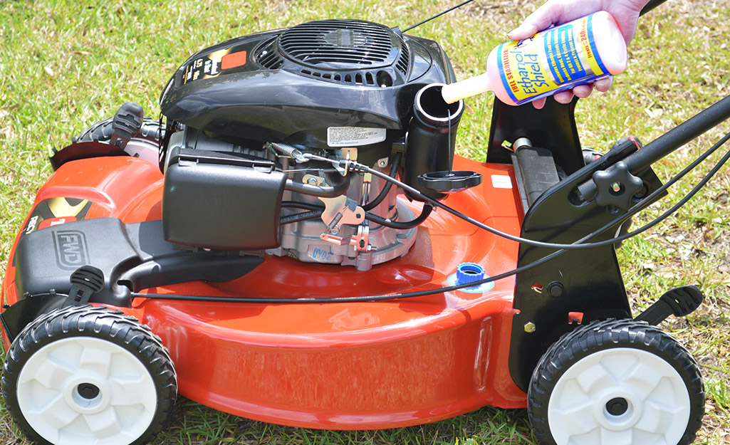 Someone pouring fuel cleaner in a lawn mower engine.