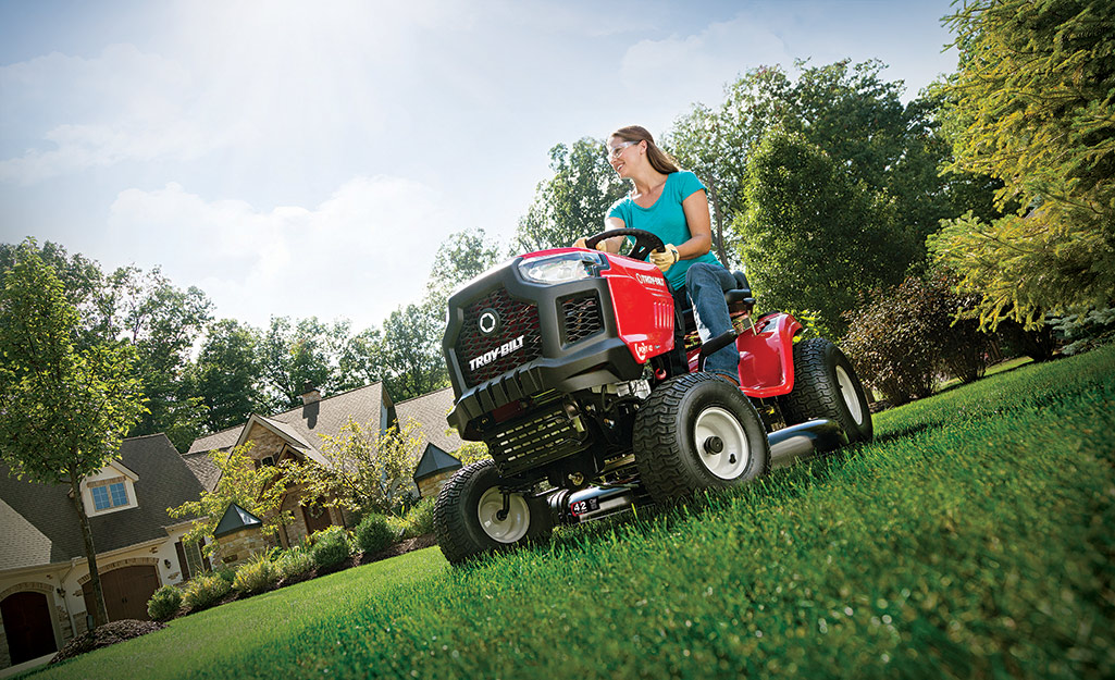 Woman cutting grass on a riding lawn mower.