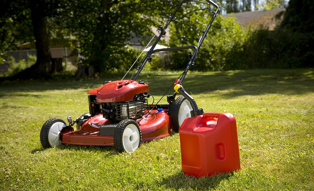 Lawn mower sitting on a lawn beside a gas canister.