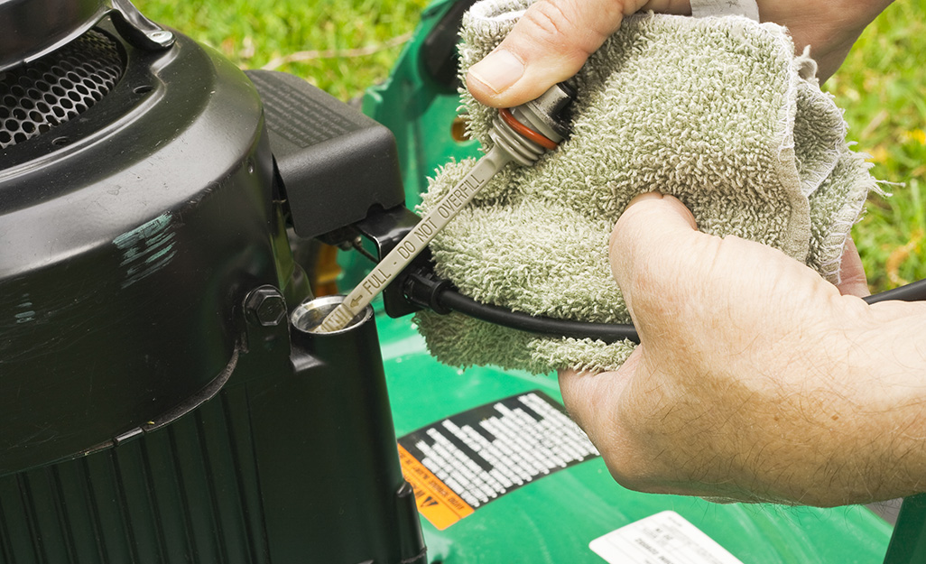Individual checking the lawn mower's oil content.